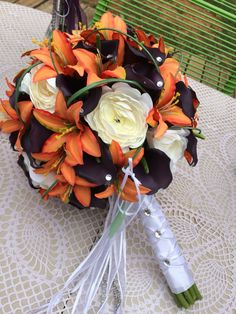 Bridal bouquet with plum Cala lilies, orange tiger lilies and white ranuculus. Lots of bling adds sparkle and elegance to this bouquet Tiger Lily Wedding, Lily Bouquet Wedding, White Rose Bouquet, Fall Wedding Bouquets, Orange Wedding Centerpieces, Lily Centerpieces, Orange Wedding Flowers, Boquette Wedding, Wedding 2015