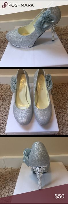Silver heels with decorative flower! Wedding/Prom Beautiful silver heels perfect for wedding/prom special occasion! Never worn, I bought them for my wedding but then chose a different pair. Size 8 Shoes Heels