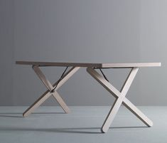 X-table by Studio Aisslinger for Böwer  is a simple light work table for office or studio space with crossed wooden base construction. The connection from a large oak-cross with the tabletop is minimalist hinges for smooth height adjustment 70-78 cm. The slope and angle of the cross give the height of the table. The length of the table is around 200-220 cm with a variety of laminate colors.