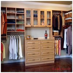 Wall mounted closet system with a double hutch, glass doors above, rouge square drawer/door fronts, in the secret apple finish. #theclosetdoctor #closet #customclosets…