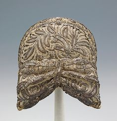 Cap | German (Bavarian peoples), early 19th century | Materials: metal, silk, cotton, paper | Originating in Munich, the 'riegelhaube' cap was the traditional headwear for Bavarian women from the mid-18th century to the mid-19th century | The stiff cardboard form is heavily adorned with metallic embroidery and sequins, requiring many hours of work | The Metropolitan Museum of Art, New York