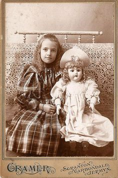 Antique photograph, 1890s. Gilded Age, Victoriana. Girl with life sized German bisque head doll. Pennsylvania.