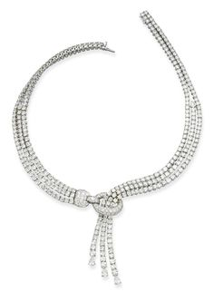 A DIAMOND NECKLACE, BY CARTIER, of lariat design composed of three brilliant-cut diamond lines gathered by a pavé-set diamond hoop to the three pear-shaped diamond terminals, mounted in rhodium plated gold, 38.0 cm inner circumference, with French assay mark for gold, signed Cartier
