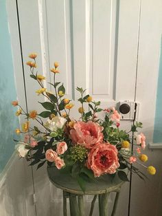 A lasting floral arrangement w/a contemporary design. The arrangement features peachy-colored peonies, gold & peach flowering branches, white garden roses and assorted greenery in a light green ceramic container. The arrangement measures approx. 21H x 22L x 13W.