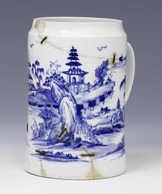 An important Vauxhall mug circa 1755 Of cylindrical form with finely turned bands above the foot and below the unusual inverted rim, painted in bright blue with a complex continuous Chinese river scene, the numerous islands with a variety of rockwork and trees, some with Chinese huts and pagodas, the grooved strap handle painted with scrollwork, 15.7cm high