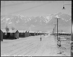 Manzanar Relocation Center, Manzanar, California. Street scene and view of quarters for evacuees of Japanese ancestry at Manzanar reception center. High Sierras in background, April 2, 1942. Photo: Department of the  Interior. War Relocation Authority. Source: National Archives.