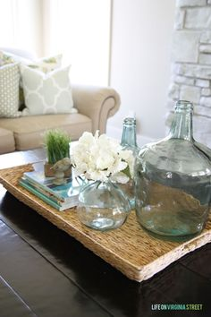 23 Summer Home Tours - such a great round-up of inspiration! Loving the look of this seagrass tray with demijohn bottles and hydrangeas!