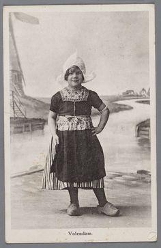 Een Volendams meisje in dracht poseert voor een geschilderd decor van het Volendammermeertje met links de molen. 1920-1930 #NoordHolland #Volendam