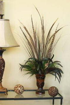 Bold And Exotic Pheasant Feather Floral Arrangement Add a bold and exotic feel to your room with this striking feather design. Tall wispy grasses with pheasant feathers add height with shorter feathers and grasses around the edge of the urn. Feather Design, Floral Design, Tuscan Decorating, Fall Decorating, Interior Decorating, Silk Floral Arrangements, Feather Crafts, Pheasant Feathers, Bird Ornaments