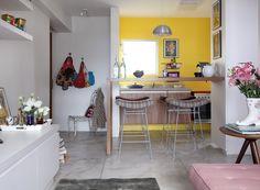Sala de estar, e ao fundo a cozinha parede de cor amarela, bancos de Fernando Jaeger, bota usada como vaso de flores na mesa lateral da sala. apartamento de 40m² da publicitária Flavia Baptistini, projetado pelo escritório Arquitetura Paralela. São Paulo (Foto: Evelyn Muller / Editora Globo)