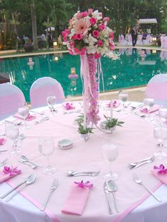 add colored fabric square on top of white table cloths? just fold napkins simple and add a flower to each?