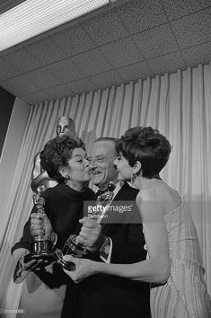 Rosalind Russell, Fred Zinnemann Holding Trophys, and Audrey Hepburn - Lucky Fred Zinnemann, surrounded by two of Hollywood's most popular ladies, Rosalind Russell and Audrey Hepburn, (right), is shown as he holds his two Oscars---one for direction, the other for the best film of the year. The film which won him all this acclaim is A Man For All Seasons.