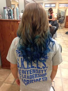 Long brown curled hair with blue dyed tips.