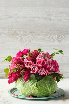Step 9 - DIY Cabbage Flower Centerpiece - Southernliving. Add greenery as filler and to conceal the rubber banded stems.