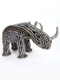 """Metal Shaving Rhino $50.00. Metal shaving art was invented by former blacksmith Amos Guta, and is made almost entirely of recycled materials. These very intricately designed pieces of work show how in the right hands, one man's trash can truly become someone else's treasure.  An enormous and strong animal, the rhinoceros symbolizes vigilance and calm. Height: 7""""  Length: 11""""  Width: 5.5""""  Artist: Peter Mwayedza  Made In: Zimbabwe"""