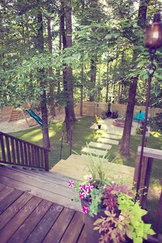 Backyard Bliss ~ This beautiful backyard was transformed from a wooded lot into a backyard oasis by first thinning out a few trees, adding a deck, fence, children's playground, patio with firepit, and finishing it off with furniture and flowers.
