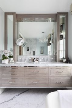 Incredible bathroom features a gray wood veneer floating vanity accented with nickel trim and hardware alongside a white marble countertop which frames his and hers oval sinks set below a built-in vanity mirror and shaving mirror flanked by a pair of mirrored countertop cabinets highlighted by blue walls, painted Zoffany Paint La Seine, over marble slab floors.
