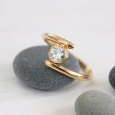 This handmade engagement ring features a shimmering Charles and Colvard Moissanite set in an asymmetrical 14k Gold band. | Handmade jewelry by TorchFire Studio