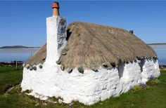 A cheerful whitewashed, thatch-roofed cottage in the Hebrides, the Western Isles of Scotland.