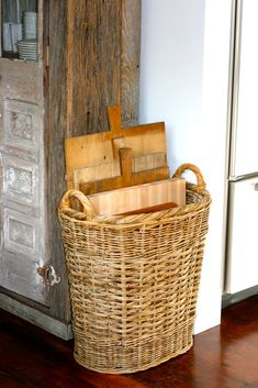 Basket filled with cutting boards. Love the tall and narrow shape of this basket