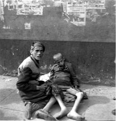 Starving children on the pavement of a ghetto street.