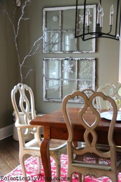 Winter snowflake window decorating idea. Silver spray painted stick decor and white snowflake ornaments on vintage windows