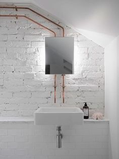 Vanity niche in the bathroom with exposed white brick wall and copper pipes that are angled …