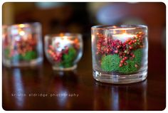 Moss, red berries and votive candles. Possible additions to the center piece arrangements?