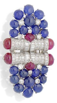 An Art Deco gem-set double-clip brooch, circa 1935. Each clip of shield-shaped design, with a cluster of circular and oval cabochon sapphires and old brilliant-cut diamond highlights, to a cylindrical panel of single and baguette-cut diamonds, accented by a buff-top ruby with ruby bead terminals, length 6.0cm. #ArtDeco #DoubleClip