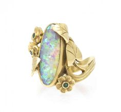 An 18 Karat Yellow Gold and Opal Ring, Lise Bennett, in an Art Nouveau style, containing one oval cabochon cut opal measuring approximately 21.75 x 7.75 mm and three mixed cut emeralds within a foliate motif setting. Stamp: 18K (maker's mark). 10.00 dwts.
