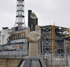 A memorial to the victims of the Chernobyl disaster in front of wrecked power station