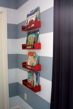I love this idea! these little red shelves are actually spice racks from ikea, painted & installed in a stacked fashion. These are only $3 each! I'm definitely doing this in my boys rooms!