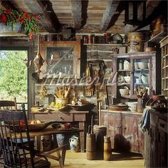 RUSTIC HOMES AND CABINS Interior shot of Primitive rustic kitchen with old corner cupboard with old pottery and cooking utensils etc log and chink walls distressed cabinets spongeware wooden bowls and utensils butter churns old tins Old Cabins, Log Cabin Homes, Cabins And Cottages, Cabins In The Woods, Primitive Homes, Primitive Kitchen, Kitchen Rustic, Primitive Decor, Western Kitchen
