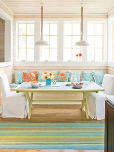 This dining nook adjacent to the kitchen features a built-in bench outfitted with a custom cushion and topped with coordinating pillows in persimmon and aqua. The simple zinc-topped table complements the casual mood of the room. (Photo: Laurey W. Glenn; Robbie Caponetto)