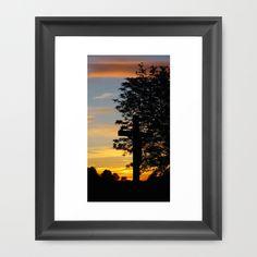 A crucifix under a tree on a wonderful sundown. Nature, sculpture, cross, tree, sky, clouds, sunset, evening, silhouettes, yellow, blue, black, light