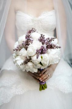 Huge blooms of ruffled white peonies with lilacs make for a truly feminine bridal bouquet.