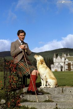 Prince Charles in day kilt attire with Balmoral Castle in the background . I love how attentive the dog is. Scotland Castles, Scottish Castles, Elizabeth Ii, Edinburgh, Palais De Buckingham, Prinz Philip, Reine Victoria, Photos Of Prince, Prince Charles And Camilla