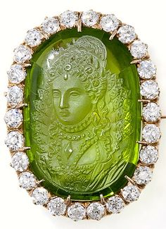 Antique Carved Peridot Cameo and Diamond Brooch Pendant, A queenly presence inhabits this exemplary and truly exquisite peridot and diamond Victorian brooch and pendant. Her royal highness is magnificently carved and captured atop a glowing green peridot weighing approximately seventeen carats and framed by twenty-six bright white, high-quality European-cut diamonds weighing two carats. This rare, magnificent and unique nineteenth century collector's item measures 1 1/4 inches by 7/8 inch.