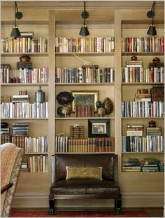 Styled Bookcase ~ I like the addition of the library lights, and the small leather bench as an interesting focal point.
