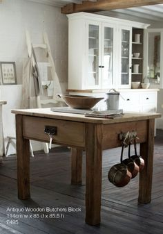 Background cupboards, pots hanging from the butcher block table