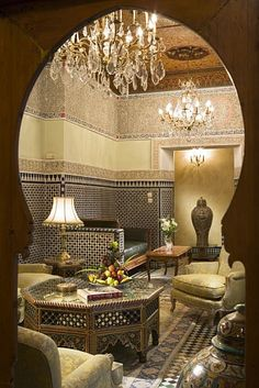 A peek through an archway into a Moroccan style lounge/seating area.