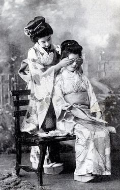 "Two Hangyoku (Young Geisha) from Tokyo playing a game of ""guess who?"" ~1910s"