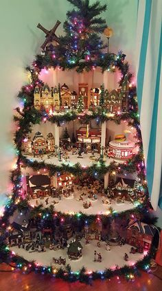 Great Idea to Display Village Houses.but with White Lights! Christmas Tree Village Display, Creative Christmas Trees, Christmas Town, Christmas Tree Themes, Christmas Villages, Diy Christmas Gifts, Christmas Projects, Christmas Holidays, Christmas Ornaments