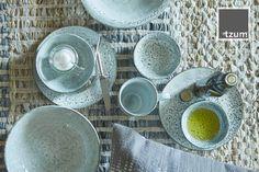 Kleurrijk servies op ons stoer ambachtelijk vervaardigd karpet van leren stroken, gemaakt van recycled restmateriaal uit de tassenproductie. Met handgeweven strepen in mix van tinten ecru, blauw en taupe.