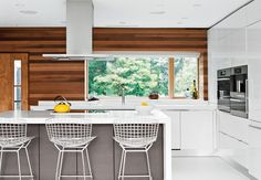 Bertoia bar stools by Knoll are tucked under the island in the Scavolini Scenery kitchen. Fernando Franco of floor specialists Garage and Beyond replaced the original wood flooring with white resin, a robust surface used in high-traffic environments. Home Decor Kitchen, Kitchen Interior, Home Kitchens, Kitchen Ideas, Bertoia, Interior Exterior, Interior Design, Kitchen Vent, Stainless Kitchen