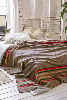 Bed on floor with striped Pendleton wool blanket