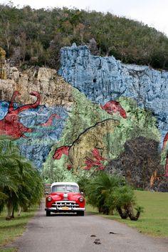 MERIDIAN TRAVEL | GOING BACK Mural de la Prehistoria, Cuba Over de foto In Cuba in de Vinales vallei bij hotel Jazmines kun je naar de Mural de la Prehistoria, die Cuba's prehistorie uitbeelden maar in 1960 in opdracht van Fidel Castro gemaakt zijn. Ik had het geluk dat er net een mooie oldtimer aan kwam rijden.