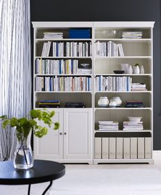 A living room with two grey ikea hemnes bookcases filled for Liatorp bookcase hack