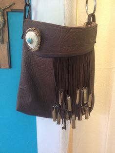 Beautiful brown leather bag with real shot gun shells , antler horn with a turquoise stone ,fringe and up-salvaged horse reins
