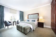 Sophisticated, glamorous interior design and decoration of a boutique hotel in Johannesburg.   Luxuriously appointed, calm, serene bedroom in soft blue colour scheme.
